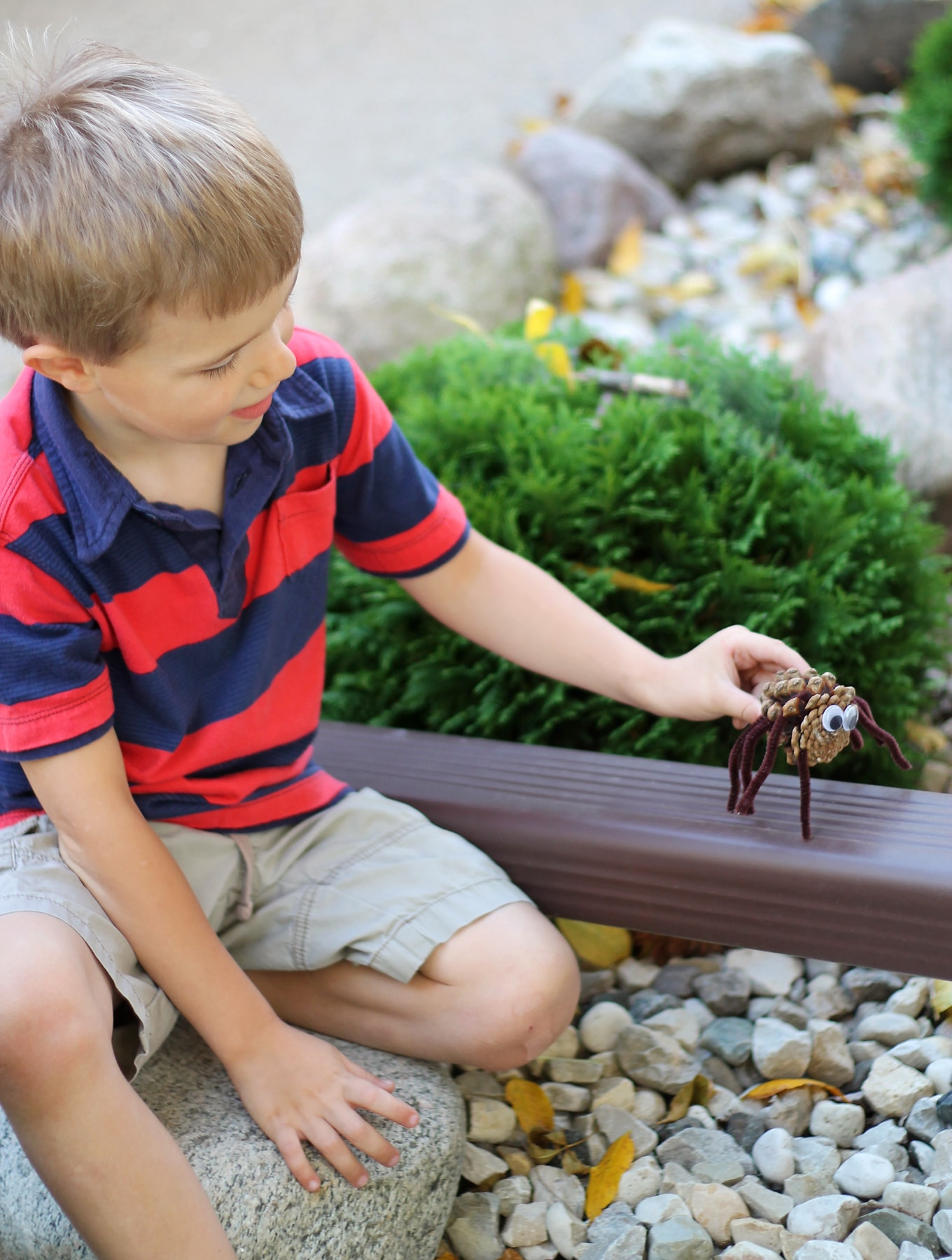 Child Playing with Pine Cone Spider Craft