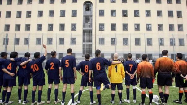 Detenuti giocano a pallone all'interno di un carcere, nell'ora d'aria