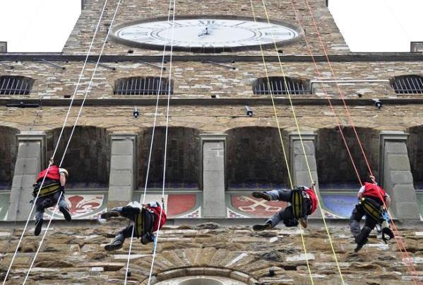 Tecnici-alpinisti  vicino all'orologio della Torre di Arnolfo di Palazzo Vecchio