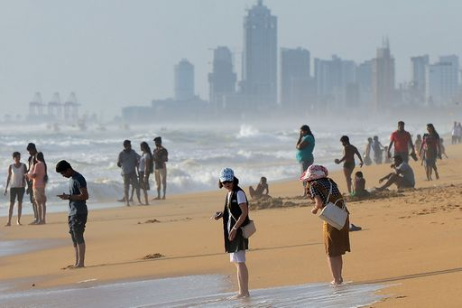 In this photograph taken on July 3, 2016, foreign tourists walk along Mount Lavinia beach on the outskirts of Colombo. Tourists have flocked back to Sri Lanka's shores since a bloody civil war ended in 2009, but environmentalists say the island is a victim of its own success as sewage from its thriving hotels pollutes its once pristine beaches. / AFP PHOTO / LAKRUWAN WANNIARACHCHI / TO GO WITH AFP STORY SRI LANKA-TOURISM-POLLUTION,FEATURE BY AMAL JAYASINGHE
