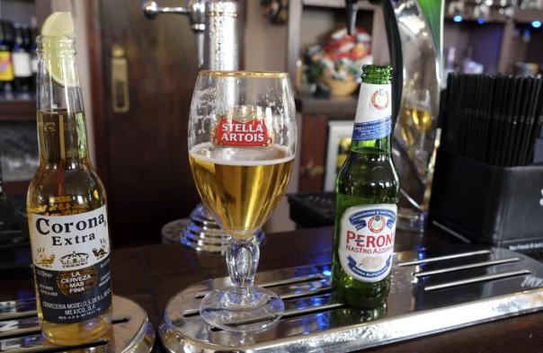 Drinks sit on the bar in a pub in London, Tuesday, Oct. 13, 2015. The world's top two beer makers agreed Tuesday to join forces to create a company that would control nearly a third of the global market. AB InBev's brands include Budweiser, Stella Artois and Corona, while SABMiller produces Peroni and Grolsch. (ANSA/AP Photo/Kirsty Wigglesworth)