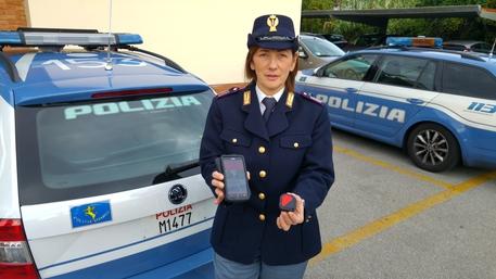 Un'agente della Polizia stradale mostra il GPS trovato sull'auto della donna