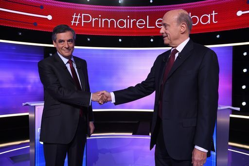 The two finalists in France's conservative presidential primary Alain Juppe (R) and Francois Fillon (L) shake hands, prior to taking part in the first televised debate between the two remaining candidates for the right-wing Les Republicains (LR) party primaries in Paris on November 24, 2016, ahead of the 2017 presidential election. France's conservative presidential favourite Francois Fillon struck a confident tone ahead of a final televised debate on November 24 with his rival Alain Juppe. A poll published on November 23 showed Fillon would win 65 percent of votes in the final primary vote on November 27 against 35 percent for the more centrist Juppe. / AFP PHOTO / POOL / Eric FEFERBERG