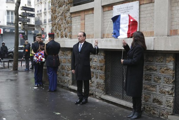 "French President Francois Hollande and Paris Mayor Anne Hidalgo unveil a commemorative plaque next to the ""La Belle Equipe"" bar and restaurant in Paris, France, Sunday, Nov. 13, 2016, during a ceremony held for the victims of last year's Paris attacks which targeted the Bataclan concert hall as well as a series of bars and killed 130 people. (Philippe Wojazer/Pool Photo via AP)"