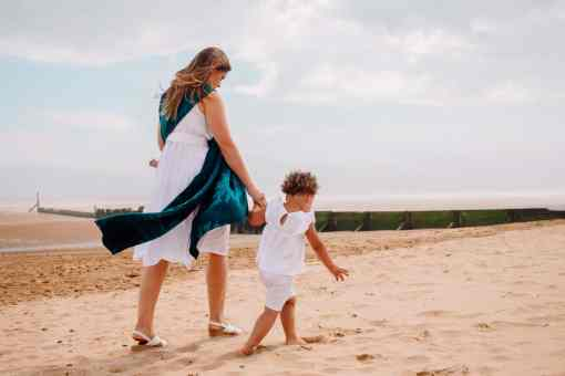 family on the beach with baby carried in a teal and navy woven wrap with a sea design