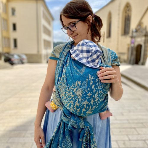 teal and gold linen blend woven wrap with birds design being worn in a front double hammock carry