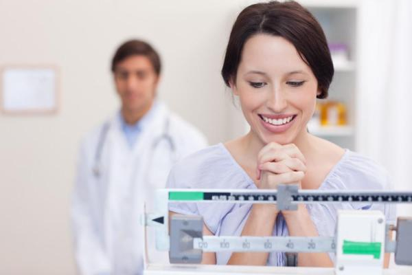 Smiling woman looking at her weight on a scale