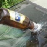 damaged windshield with beer bottle stuck in it