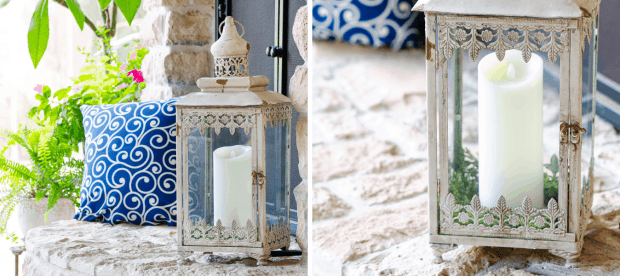 White rustic lantern with pillar candle on outdoor stone fireplace