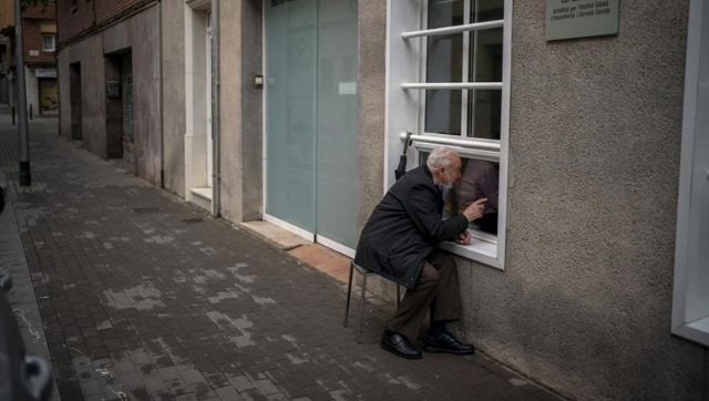 In Spain an elderly couple separated after the pandemic overcome grief through a glass pane