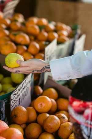 crop faceless person buying lemon in market