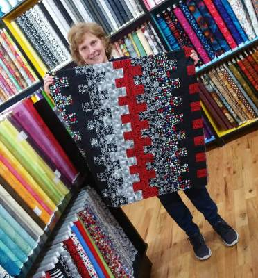 Picture of Deb holding the featured pattern for the week called Zipper