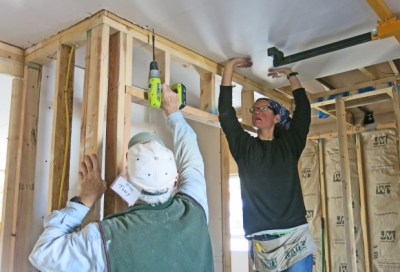 Two workers framing a room at a Habitat for Humanity build site