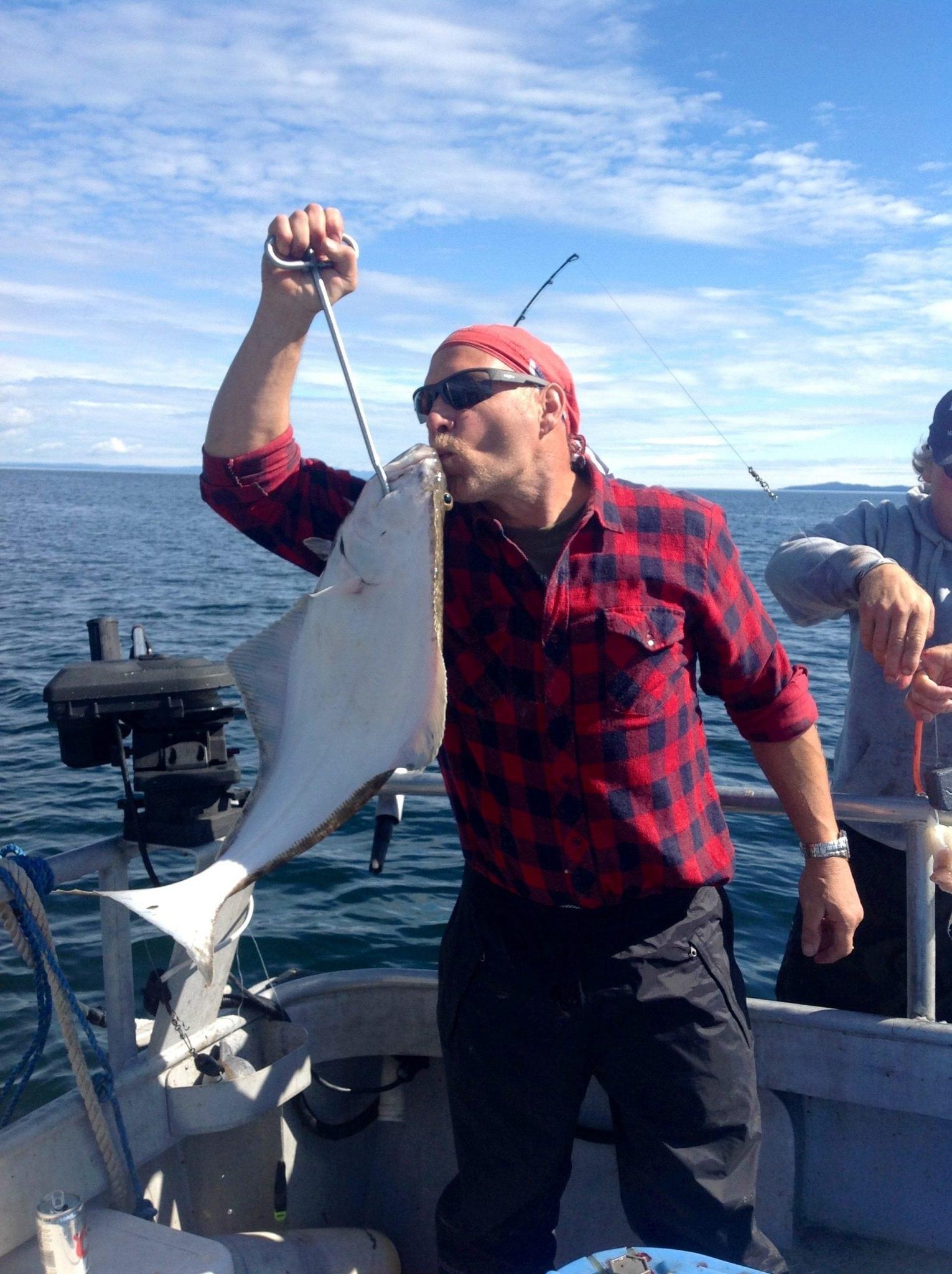 Kodiak Halibut Fisherman Kissing his catch on Fish N' Chips Charters