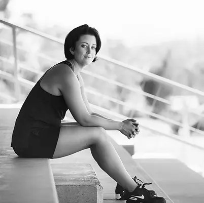 Angie sitting on stairs in black and white