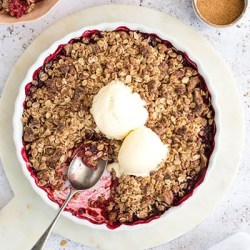 Raspberry & Rhubarb Crisp with ice cream in a white pie dish