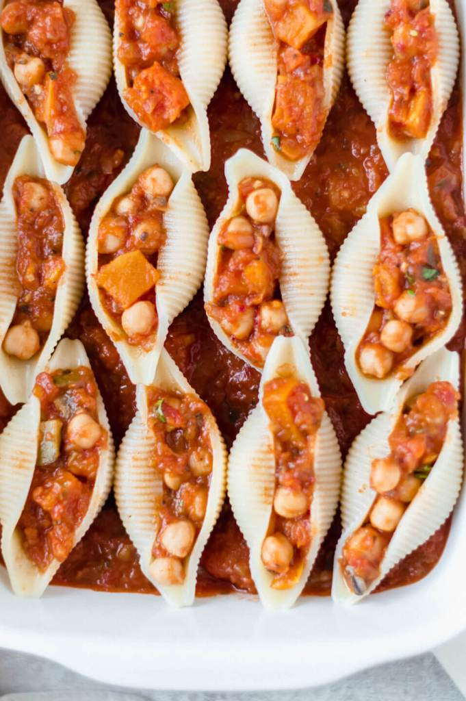Stuffed pasta shells in tomato sauce in a white dish