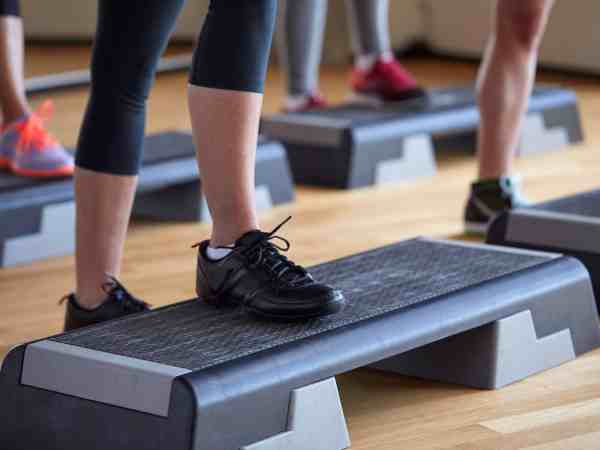 fitness, sport, people, step aerobics and lifestyle concept – close up of women legs exercising with steppers in gym