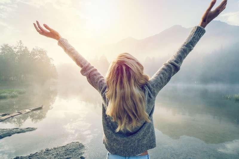 Frau steht an einem See und streckt die Hände nach oben
