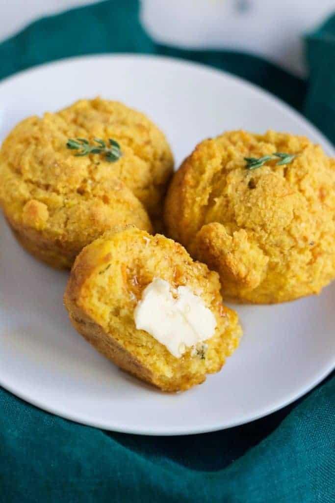 vegan sweet potato cornbread with butter melting on white plate