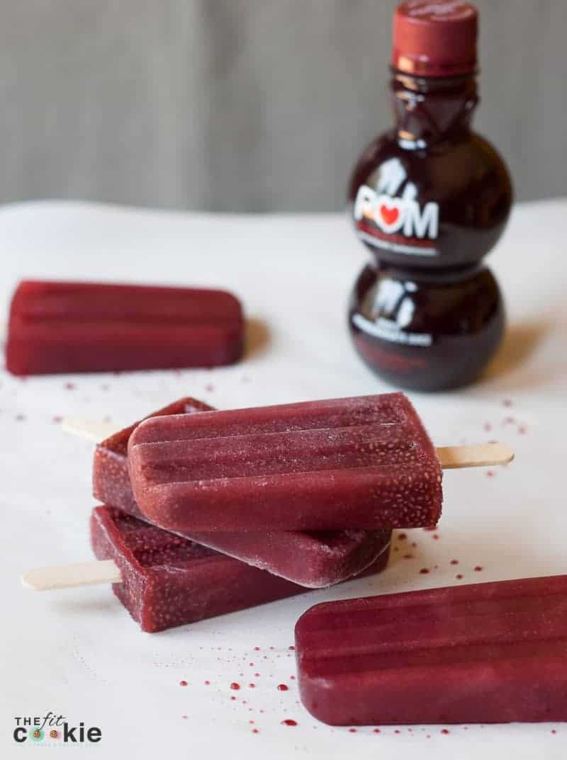 several pomegranate popsicles on a table beside POM juice