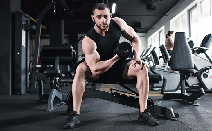 Man Doing A Concentration Curl Exercise For Biceps