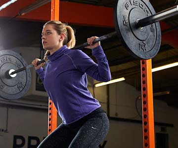 Woman Using Squat Rack For Fitness