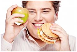 Picture of a foodie man with a beef burger and an apple