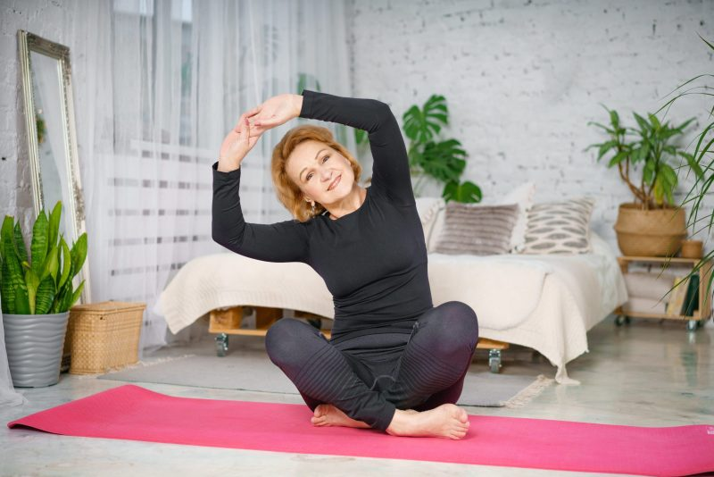 Training clients who are 56+: senior woman performing a stretch on a yoga mat and smiling.