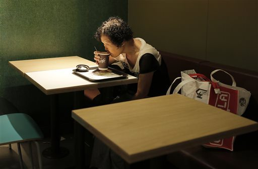 In this Friday, Nov. 20, 2015 photo, Mary Seow drinks coffee at a 24-hour McDonald's branch where she began sleeping about four weeks ago after she noticed others doing it in Hong Kong. Seow, a Singaporean woman who went missing nearly five years ago, has been reunited with her son after her plight was reported in an Associated Press story about people who sleep at 24-hour McDonald's outlets in Hong Kong. (AP Photo/Vincent Yu)