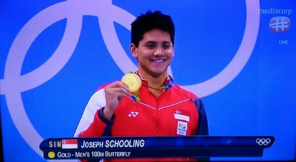 Joseph Schooling holding Olympic gold medal 100m butterfly