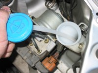 Washer fluid is checked and filled in a reservoir marked with a windshield wiper diagram.
