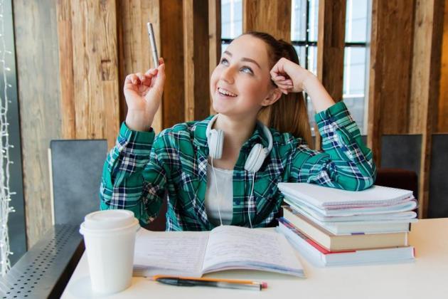 Studentin denkt nach Bücher im Vordergrund
