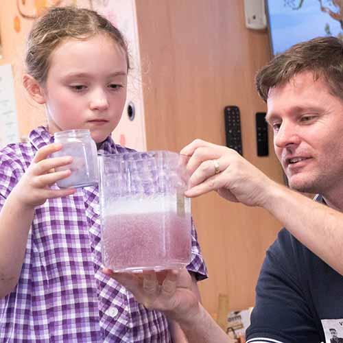 A student watching a purple liquid fizz