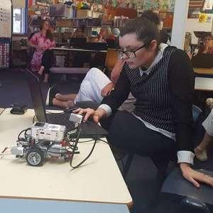 A teacher programming a Lego Mindstorms Robot