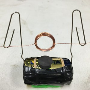 A coil of wire suspended over a D battery by two paperclips