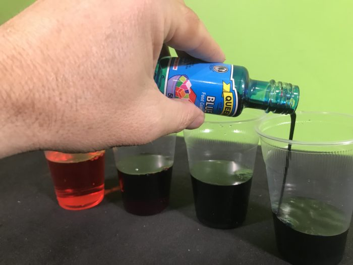 Make coloured petals science experiment - pouring food colouring into a cup