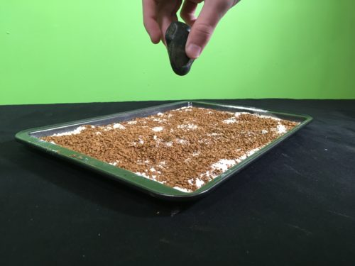 Model Meteorite Strikes Science Experiment - throwing first rock into baking tray(1)
