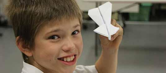 A boy holding a paper plane