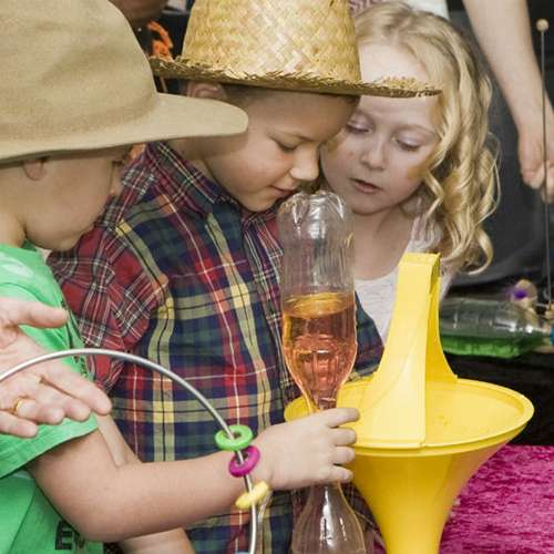 Three children looking at a coin spin down a yellow vortex funnel whilst holding science toys