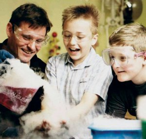 A man pouring dry ice fog out of a beaker whilst two smiling kids watch