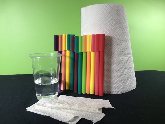 A plastic cup of water, paper towelling, textas an strips of paper towelling on a black desk in front of a green background