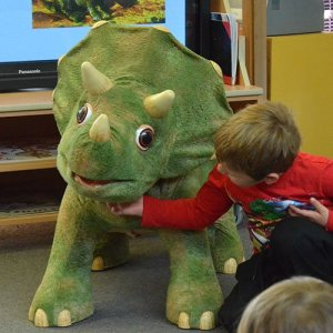A child scratching the throat of a large green triceratops animatronic puppet