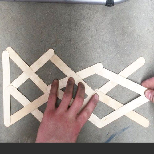 lattice of many wooden sticks with hands showing where to hold the sticks