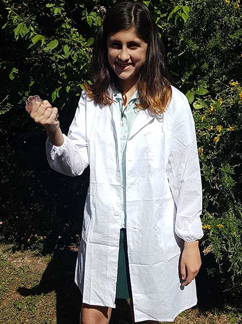 A girl smiling and wearing a lab coat
