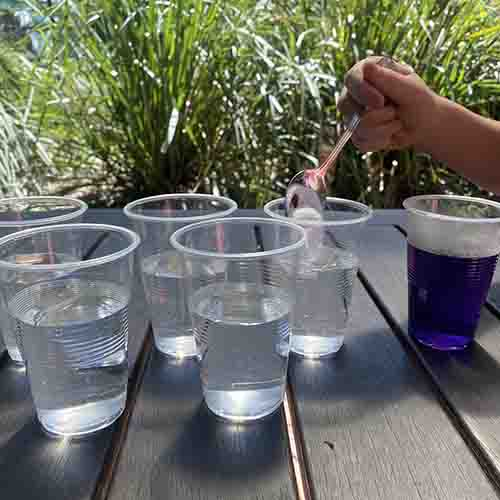 Pouring a spoon of bicabonate soda into a plastic cup filled with water