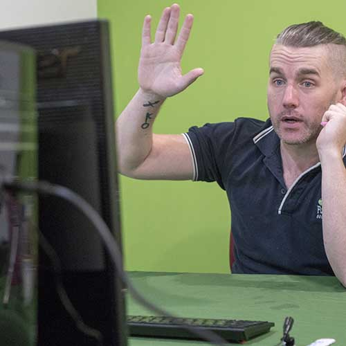A person sitting at a desk with their hand up whilst looking at a computer monitor