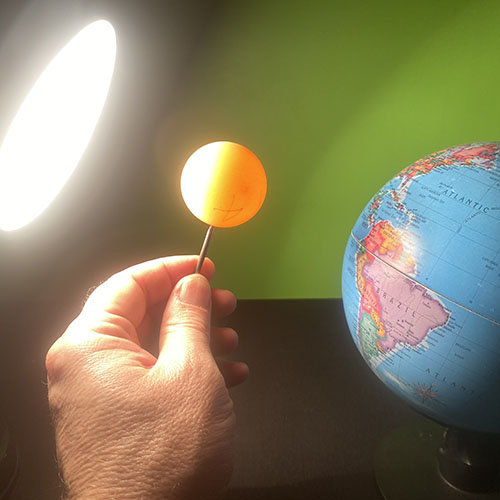 A model of the Earth illuminated by a lamp. A hand is holding a ping pong ball on top of a nail inbetween.
