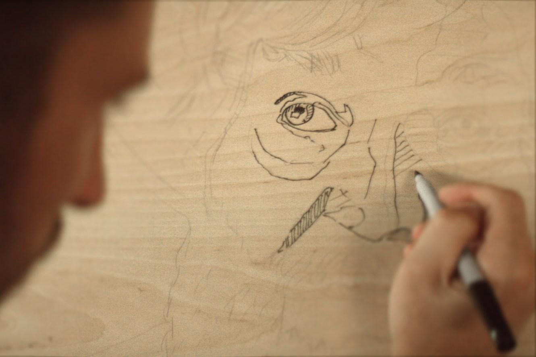 Andrew dessine les contours du vsage de Georges sur une planche