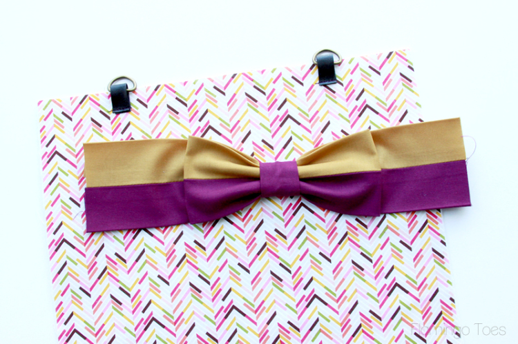 Sewing bow to front of bag